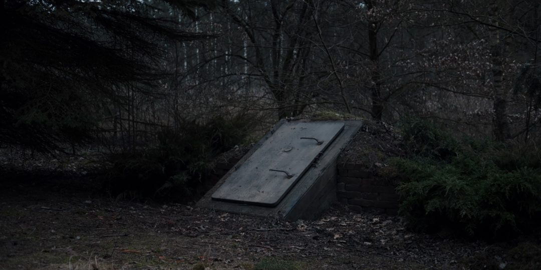 (1) A mysterious bunker, (probably) with weapons and pictures inside. We don't see a continuous shot entering the bunker, so it's possible the next scene isn't inside the bunker.