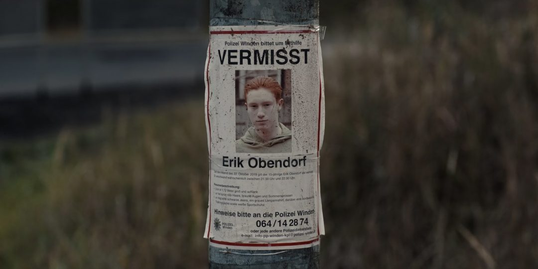 (21) Jonas also looks at the poster that declares Erik Obendorf missing