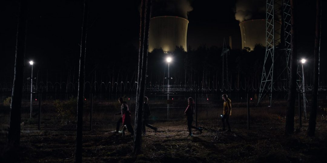 (63) The kids walk past the nuclear plant