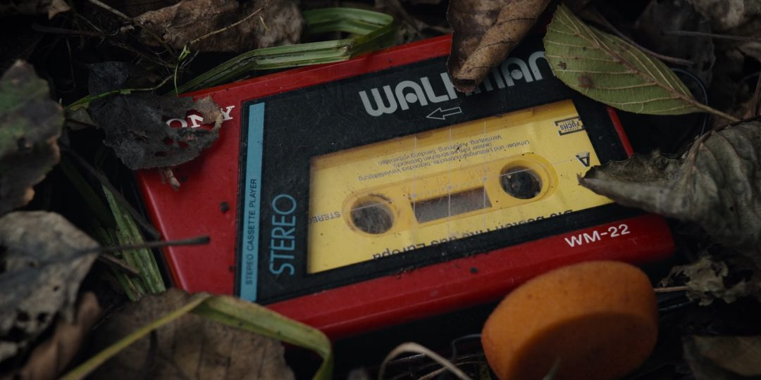 (94) A Walkman from the 1980s lies next to the body